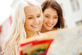 Beautiful girls looking into tourist map in city holidays and tourism concept the Stock Photo
