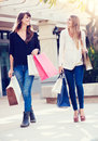 Beautiful girls with shopping bags walking at the mall Stock Images