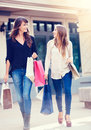 Beautiful girls with shopping bags walking at the mall Royalty Free Stock Photos