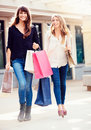 Beautiful girls with shopping bags walking at the mall Stock Image