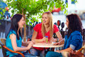 Beautiful girls sitting on cafe terrace three Royalty Free Stock Photography