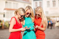 Beautiful girls with smartphones in the city holidays and tourism modern technology concept blonde Royalty Free Stock Image