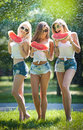 Beautiful girls with sunglasses eating fresh watermelon laughing. Happy young women holding watermelon slices outdoors Royalty Free Stock Photo