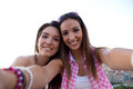 Beautiful girls taking a selfie on the roof at sunset outdoor portrait of Royalty Free Stock Photo
