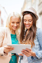 Beautiful girls toursits looking into tablet pc holidays and tourism concept in the city Stock Photos