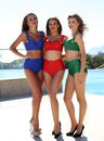 Beautiful girsl in colorful elegant swimsuites, posing beside swimming pool Royalty Free Stock Photo