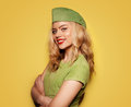 Beautiful glamorous blond woman in a trendy green summer ensemble standing with folded arms and a jaunty expression on yellow Royalty Free Stock Image