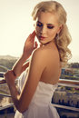 Beautiful glamour bride with blond hair in elegant dress posing at the balcony Royalty Free Stock Images