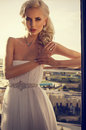 Beautiful glamour bride with blond hair in elegant dress posing at the balcony Stock Images