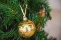 Beautiful golden ball decoration toy on the artificial Christmas tree Royalty Free Stock Photo