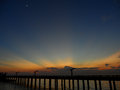 Beautiful golden after glow and the crescent moon on dark blue sky over the bridge to the sea Royalty Free Stock Photo