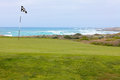 Beautiful golf hole green with flag on California ocean coast Royalty Free Stock Photo