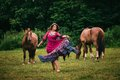 Beautiful gypsy in violet dress with horses Royalty Free Stock Photography