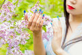 Beautiful hands girls with fake long nails with pictures holding a branch of lilac in the garden, on your lips red lipstick Royalty Free Stock Photo