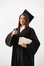 Beautiful happy african female graduate smiling showing okay holding books looking at camera. Royalty Free Stock Photo