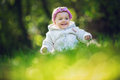 Beautiful happy baby girl sitting on green grass Royalty Free Stock Photo