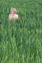 Beautiful happy blonde woman smiling outdoors on green wheat field in summer nature Royalty Free Stock Photo