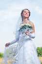 Beautiful happy bride looks down Stock Images