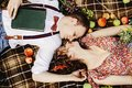 beautiful happy bride and stylish retro groom lying on tweed blanket, cuddling and relaxing, picnic in sunny meadow Royalty Free Stock Photo