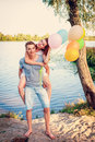 Beautiful happy couple with balloons hugs she hopped on his back outdoors river bank Stock Images
