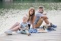 Beautiful happy family having picnic near lake Royalty Free Stock Photo