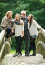 Beautiful happy family standing together in a bridge in the woods portrait of Stock Image