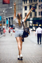 Beautiful happy girl with a backpack bag walking on city street and having fun. Woman walk hand up wearing sport summer outfit Royalty Free Stock Photo