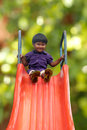Beautiful happy indian girl kid on park slider on a summer day this s photo is green background with clipping path showing Stock Images