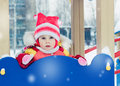 Beautiful happy kid in the red warm clothing winter outdoors Royalty Free Stock Photo