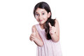 Beautiful happy little girl with long dark hair and dress looking at camera with thumbs up. Royalty Free Stock Photo