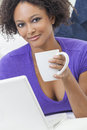 Beautiful happy mixed race african american girl young woman laying down sofa using laptop computer drinking tea coffee Stock Image