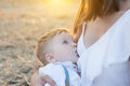 Beautiful happy mother breastfeeding her baby boy outdoor. Royalty Free Stock Photo