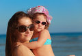 Beautiful happy mother and kid girl on blue sea backgroun Royalty Free Stock Image