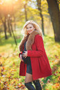Beautiful happy pregnant woman staying in autumn park touching her belly and enjoying expecting of baby. Royalty Free Stock Photo