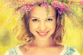 Beautiful happy slavic girl in a wreath of summer flowers face on nature Royalty Free Stock Photos