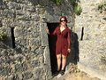 A beautiful happy smiling young tourist standing beside one of the doorways or entrances to the ancient stone Klis Fortress
