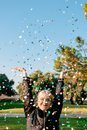 Beautiful happy woman at celebration party with confetti falling everywhere on her Royalty Free Stock Photo