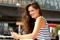 Beautiful happy woman holding smart phone outside Royalty Free Stock Photo