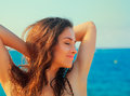 Beautiful happy woman joying with closed eyes on blue sea and sky background closeup portrait Stock Photography