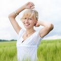 Beautiful happy woman in nature enjoying the beauty of standing a green field with her arms raised smiling happily Stock Images