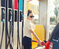 Beautiful happy woman at old fashioned gas station young smiling fills petrol car on sunny summer day Stock Photography