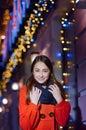 Beautiful happy woman in orange coat walks on night city Royalty Free Stock Photo