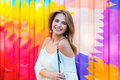 Beautiful happy woman with perfect smile posing agains colorful metal wall and looking into camera Royalty Free Stock Photo