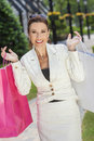 Beautiful happy woman with pink and white shopping bags fashionable colorful Royalty Free Stock Photography