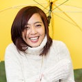 Beautiful happy young asian woman sheltering under a yellow umbrella in a warm polo neck sweater standing laughing at the camera Royalty Free Stock Photo