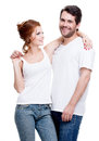 Beautiful happy young couple dressed in blue jeans and white undershirt isolated on white background Royalty Free Stock Photos