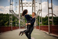 Beautiful happy young couple of man and woman spinning outdoor on bridge Royalty Free Stock Photo