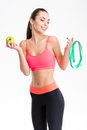 Beautiful happy young sportswoman holding measuring tape and an apple in pink top black leggings isolated over white Royalty Free Stock Image