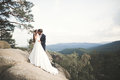 Newlyweds kissing on the beautiful Cliff against the backdrop of the ocean