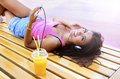 Beautiful happy young woman with juice listening music on phone Royalty Free Stock Photo